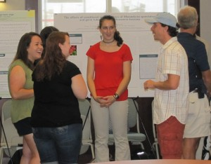 Some students from the 2012 REU show off their research at the symposium.