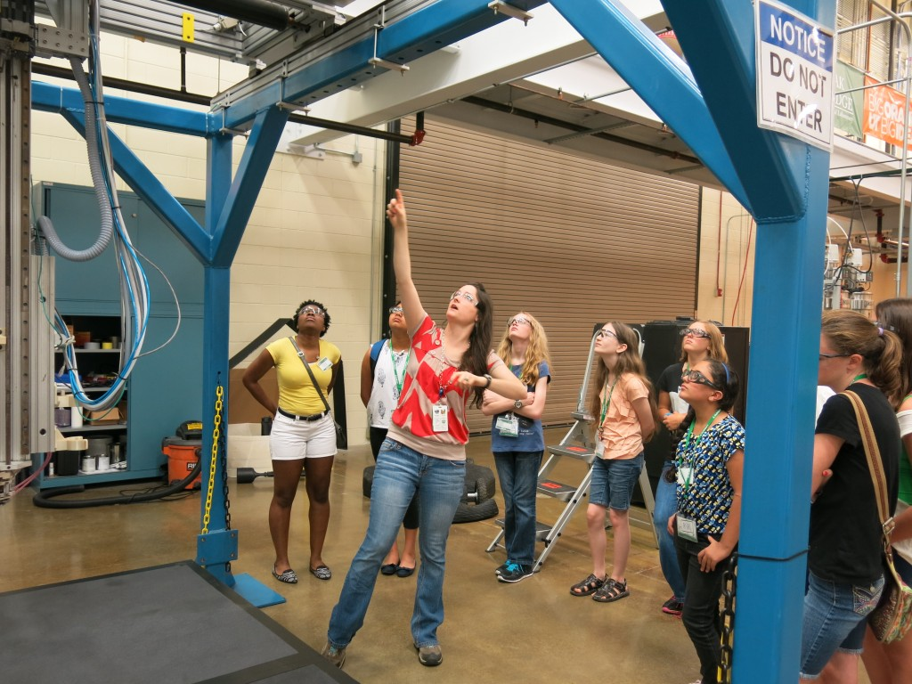 Amy Elliott (center, red shirt) shows the girls a 3D printer that's large enough to print a human-sized chair.