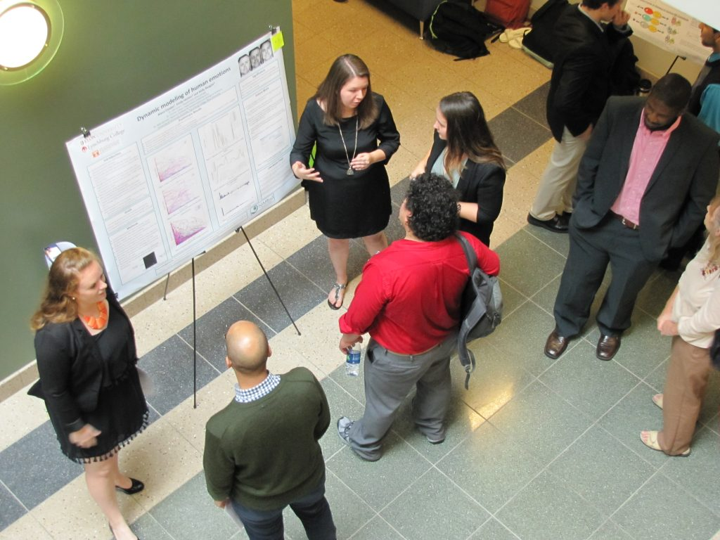 SRE participants Kelly Regan (left), Alana Cooper and Emily Horton (right of poster) present their work on dynamic modeling of human emotions.